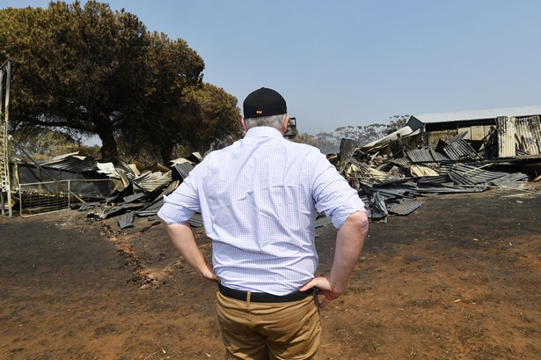 PM Morrison surveys damage caused by massive bushfires on Kangaroo Island in southern Australia; he is increasingly under fire over his handling of the crisis [David Mariuz/AAP Image via Reuters]