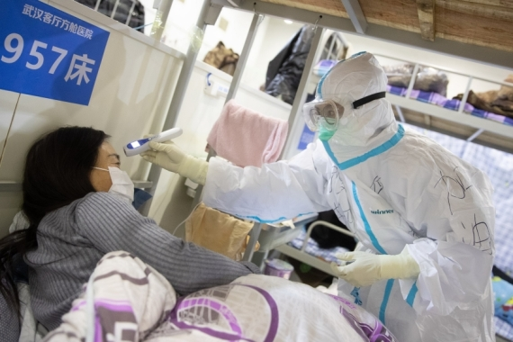 Medical staff in protective suits attend to patients at Wuhan Fang Cang makeshift hospital in Wuhan, Hubei Province, China, [File: EPA-EFE]