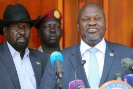 Former rebel leader Riek Machar flanked by President Salva Kiir addresses a news conference at the State House in Juba [Jok Solomun/Reuters]