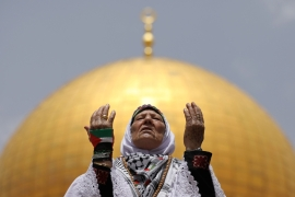 The Dome of the Rock is seen in the background as a Palestinian woman prays on the compound known to Muslims as al-Haram al-Sharif and to Jews as Temple Mount [Ammar Awad/Reuters]