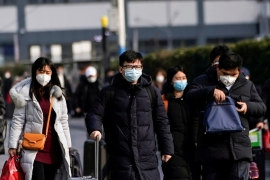 Passengers wearing masks walk at the Shanghai railway station in China, as the country is hit by an outbreak of the novel coronavirus, February 9, 2020. [Aly Song/Reuters]