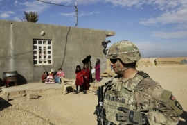 US Army soldiers speak to families in rural Anbar on a reconnaissance patrol near a coalition outpost in western Iraq on January 27, 2018 [File: AP/Susannah George]