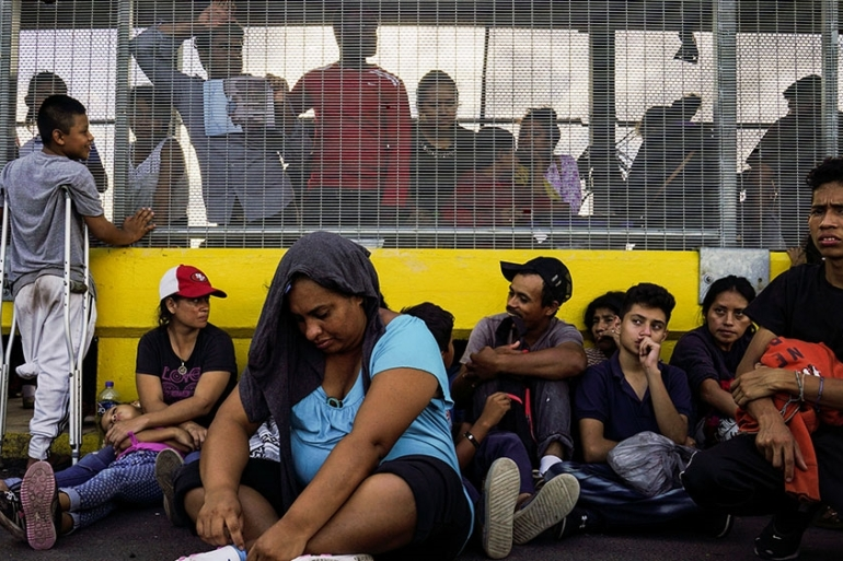 A group of migrants, who returned to Mexico to await their US asylum hearing, block the Puerta Mexico border crossing bridge to demand a speedier asylum process in Matamoros, Mexico [Veronica G Cardenas/Reuters]