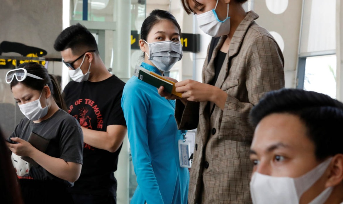 Passengers and a staff member of Vietnam Airlines wear masks while waiting to board at Danang airport. [Kham/Reuters]