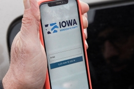 Precinct captain Carl Voss of Des Moines displays the IDP caucus reporting app on his phone outside the IDP headquarters in Des Moines, Iowa [Nati Harnik/AP Photo]