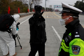 A police officer attempts to prevent the photographer from taking pictures at a checkpoint at the Jiujiang Yangtze River Bridge, in Jiangxi province, China [Thomas Peter/Reuters]