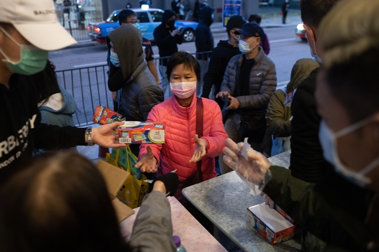 The coronavirus has sparked fear in Hong Kong where memories of the 2003 SARS outbreak remain vivid, but it has also reignited long-simmering animosities [Jerome Favre/EPA]