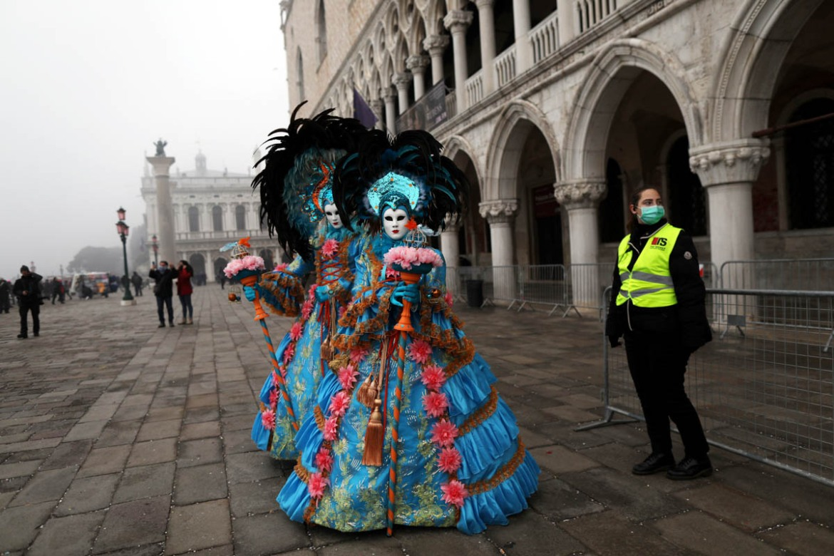 A policewoman in a mask stands next to carnival revellers at the Venice Carnival. The carnival's last two days were cancelled as cases of infection with coronavirus rose in Italy. [Ohad Zwigenberg/Reuters]