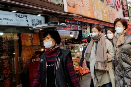 Women wearing masks as a preventive measure against the coronavirus walk at a traditional market in Seoul, South Korea, February 20, 2020 [Heo Ran/Reuters]