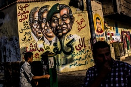 Egyptian men walk past graffiti showing the faces of Hosni Mubarak, right, Hussein Tantawi, Amr Mussa and Ahmed Shafik in Tahrir Square on June 14, 2012 [File: Getty Images]