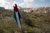 A representation of a map with the colours of the Palestinian flag reading 'Jerusalem is the eternal capital of Palestine' is placed on a fence during a protest, in the village of Bilin in the Israeli-occupied West Bank [Mohamad Torokman/Reuters]