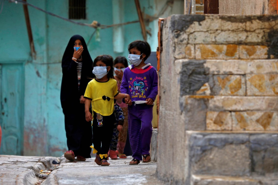 Iraqi children walk near a religious school where the first coronavirus case was detected in the holy city of Najaf. [Alaa al-Marjani/Reuters]