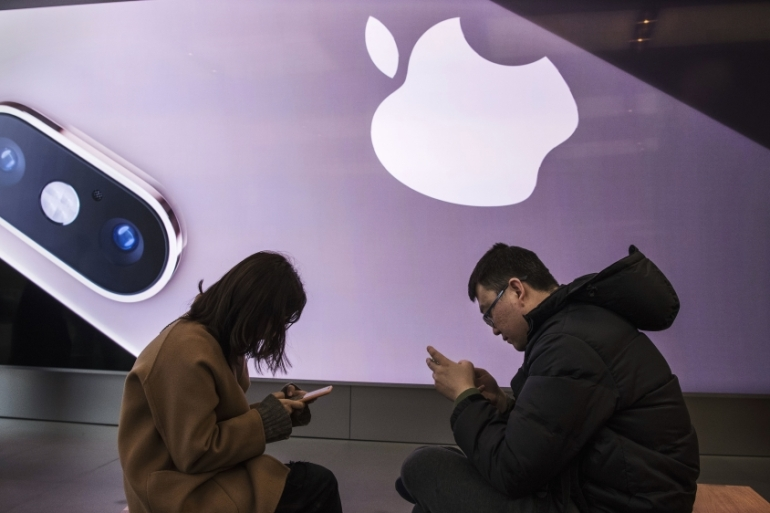 Customers learn how to use iPhones at an Apple Store in China, where the company says that despite the coronavirus outbreak, its productions facilities have reopened [File: Kevin Frayer/Getty Images]