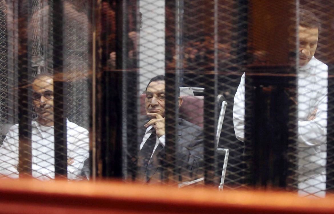 Egypt's former President Hosni Mubarak sits next to his sons Gamal, left, and Alaa, right, inside a dock at the police academy on the outskirts of Cairo May 21, 2014. [Reuters]