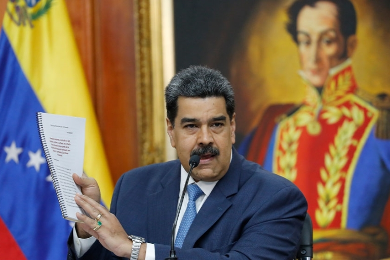 Maduro holds up a copy of his country's case taken to the International Criminal Court regarding US sanctions during a news conference at Miraflores presidential palace in Caracas, Venezuela [Ariana Cubillos/AP Photo]