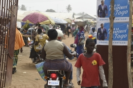 A motorbike taxi drive past campaign banners of Togolese President of the governing Union for the Republic party, Faure Gnassingbe, at the Sokode Market in northern Togo. [Pius Utomi Ekpei/AFP]