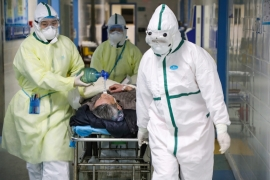 Medical workers in protective suits move a patient at an isolated ward of a hospital following an outbreak of the novel coronavirus in Wuhan, Hubei province, China February 6, 2020 [Reuters]