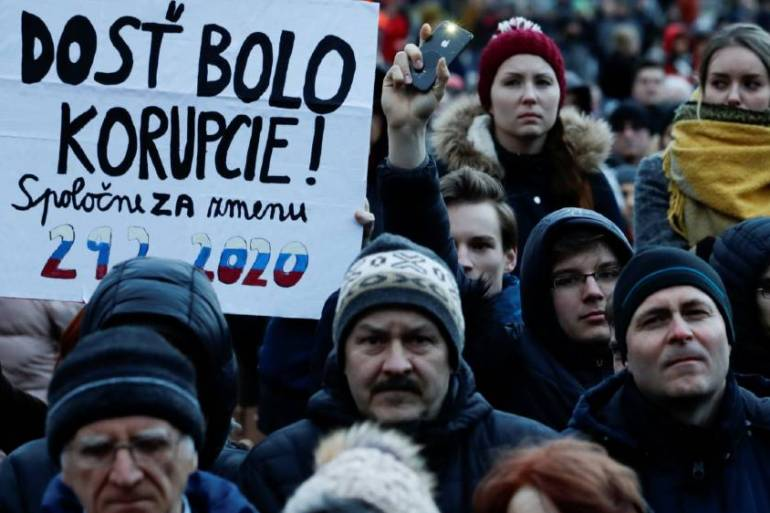 Demonstrators in Bratislava hold a banner reading: 'Enough with corruption' [David W Cerny/Reuters]