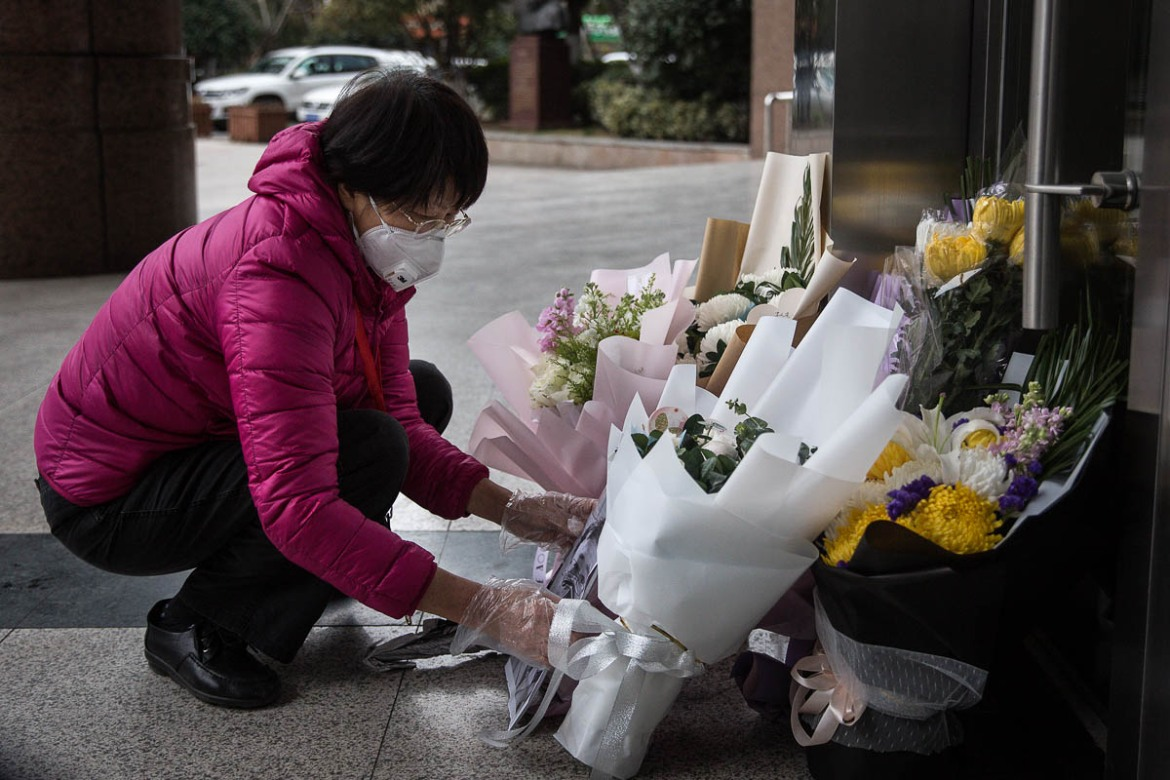 A resident lays flowers in tribute to Dr Li Wenliang at the hospital where he worked. Li, who died of the disease and has been hailed as a national hero, was reprimanded by officials after warning about the virus in December. [Getty Images]