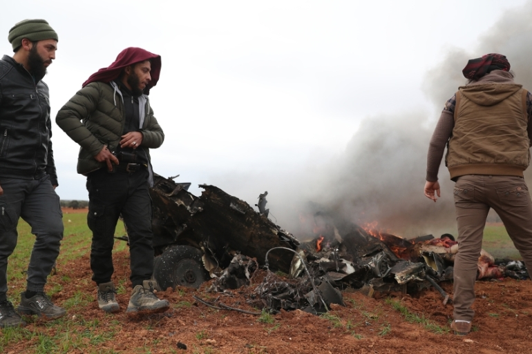 Syrian rebel fighters gather around the burning remains of a military helicopter after it was shot down northwestern Syria  [Omar Haj Kadour/AFP]
