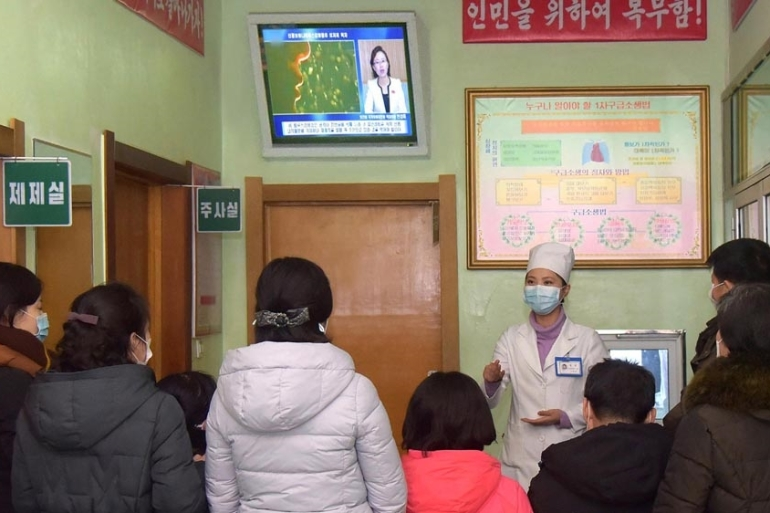 A photo released by the official North Korean Central News Agency (KCNA) shows a health worker speaking to people about the coronavirus, in Pyongyang [EPA]