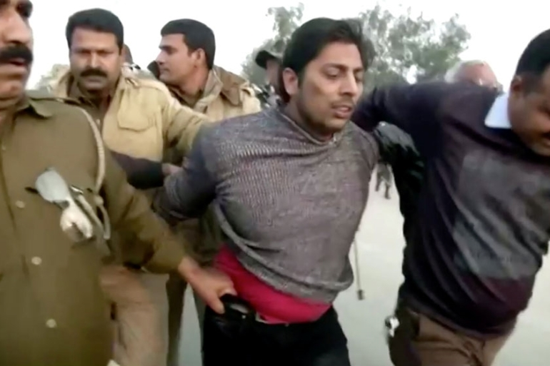 Police officers detain the suspect, identified as Kapil Gujjar, who fired multiple shots at Shaheen Bagh protest site [Reuters]
