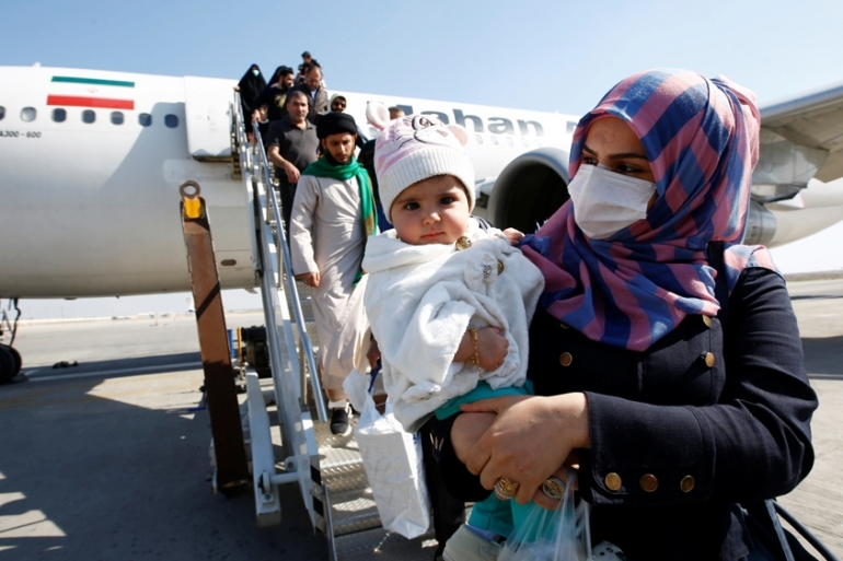 Passengers wearing protective masks disembark from a plane upon their arrival at Najaf airport, Iraq [Alaa al-Marjani/Reuters]