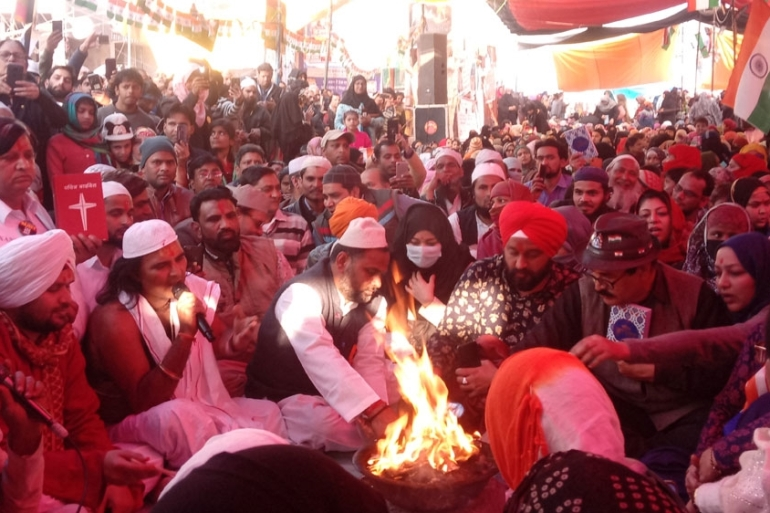 A Hindu priest lights the holy fire at Shaheen Bagh as people from other faiths participate in prayers [Sumaira Rizvi/Al Jazeera]