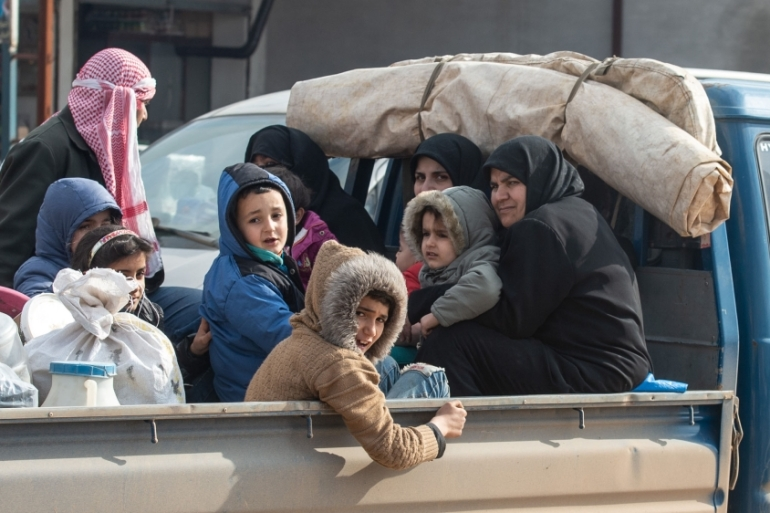 A displaced Syrian family ride in the back of a truck loaded with family's possessions on February 22, 2020, in Idlib, Syria [Burak Kara/Getty]