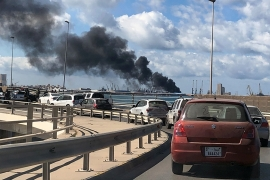 Smoke rises from a port in Tripoli after being attacked [Ahmed Elumami/Reuters]