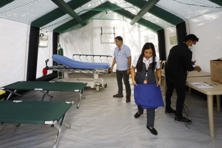 Staff at a hospital in Manila prepare the equipment of an isolation tent installed for patients who will manifest symptoms that could be investigated for coronavirus [Rolex dela Pena/EPA]