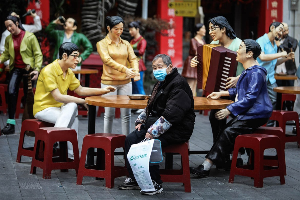 A masked man sits in an art installation in a traditional food street in Wuhan. [Getty Images]
