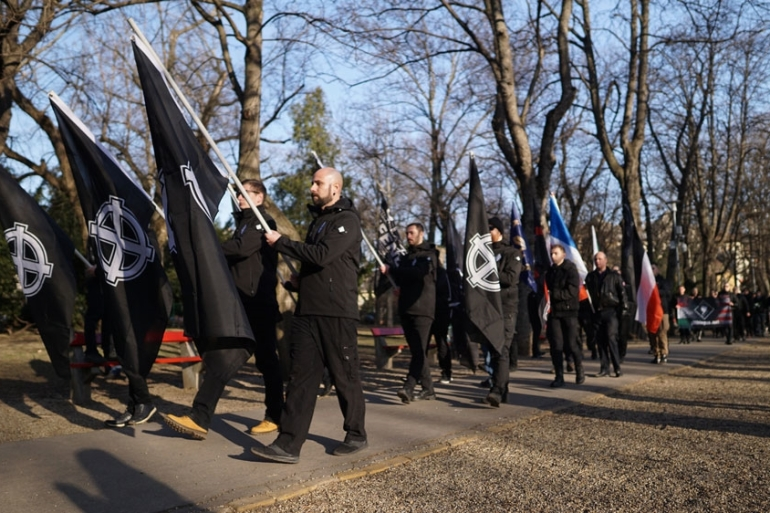 Draped in black, participants carrying flags of their respective far-right movements from across Europe [Michael Colborne/Al Jazeera]