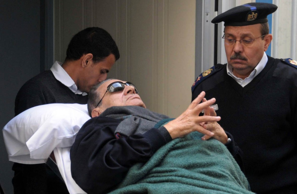 Former Egyptian President Hosni Mubarak lies on a gurney bed while leaving the courtroom at the police academy, where he was on trial, in Cairo on January 2, 2012. [Reuters]