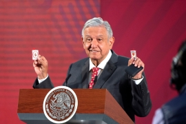 Mexico's President Andres Manuel Lopez Obrador holds his amulets, which he says serves him as 'protective shields' against the coronavirus disease, but to protect the Latin American country's economy, he has pledged billions of dollars [Mexico's Presidency/Handout via Reuters]