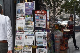 A man browses Mexican newspaper headlines during lunchtime in Mexico City, where newsstands display lurid photos of the dead along with sports stars and erotic models in popular newspapers known as nota roja or 'red news'  [Suman Naishadham]/Al Jazeera]