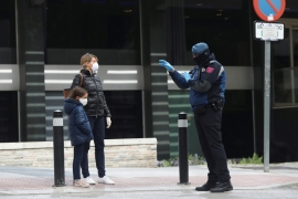 A police officer talks to a woman outside a hotel that has been set up to treat non-critical coronavirus patients during the coronavirus disease (COVID-19) health emergency in Madrid, Spain, March 19, 2020 [Susana Vera/Reuters]
