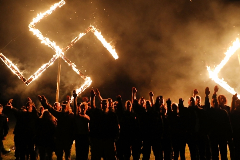 Members of the National Socialist Movement, one of the largest neo-Nazi groups in the US, hold a swastika burning after a rally in 2018 in Georgia [File: Spencer Platt/Getty Images/AFP]
