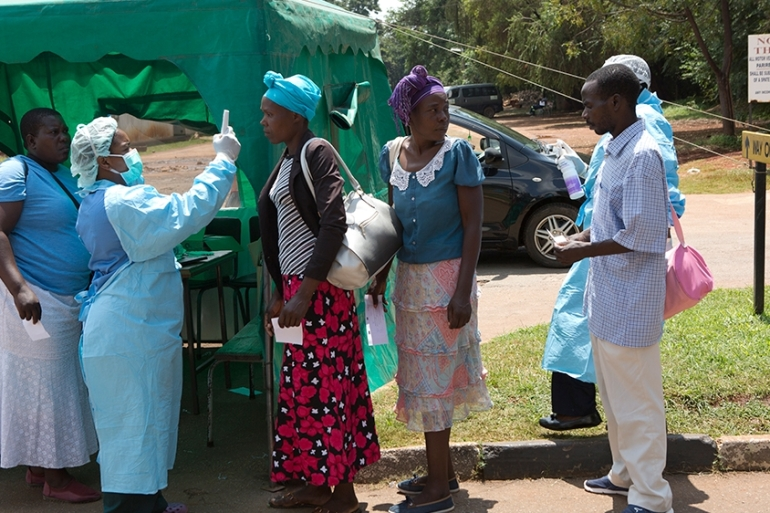 Health workers screen people visiting a public hospital in Harare, Zimbabwe [Tsvangirayi Mukwazhi/AP]