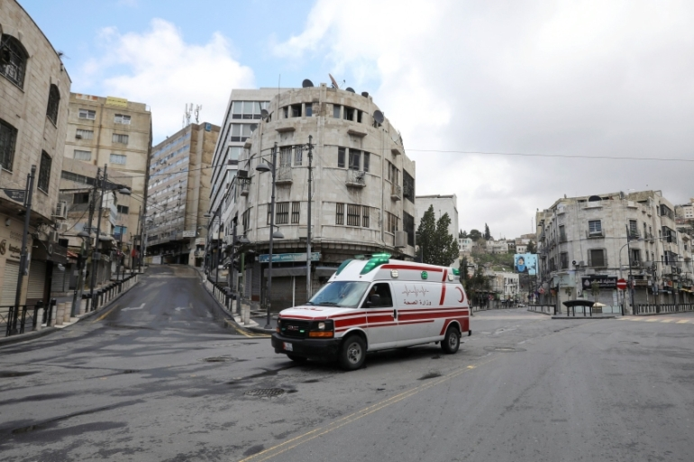 An ambulance is seen on an empty street in Amman after the start of a nationwide curfew [Muhammad Hamed/Reuters]