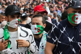 Demonstrators cover their faces with national flags during an anti-government protest in Algiers last March [File: Ramzi Boudina/Reuters]