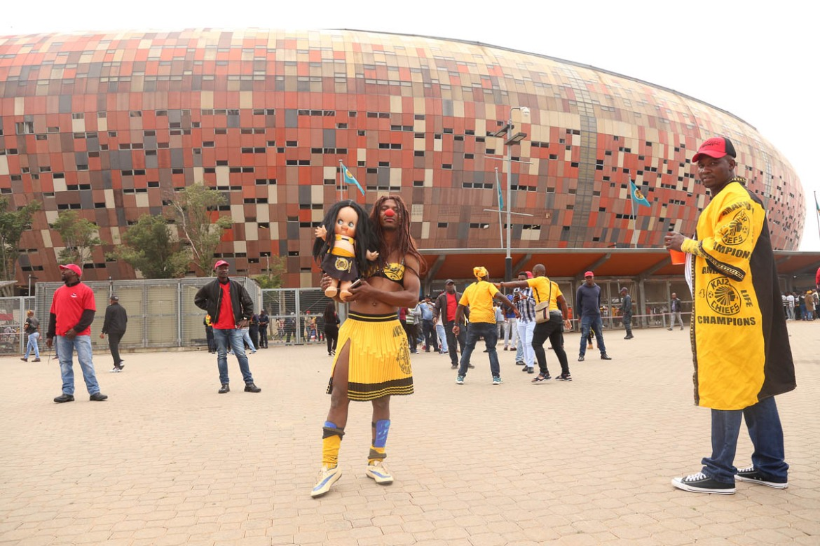 "Salmon, a Kaizer Chiefs fan, holds a doll outside the stadium. He believes the doll represents ""love and peace"" - the club's slogans. Cross-dressing is big among supporters, especially Orlando Pirates fans, some of whom argue that dressing like a woman channels the power of female fertility and connection to the creation of life. Many of their fans see the Pirates as the ""mother"" of football teams. [Antony Kaminju/Al Jazeera]"