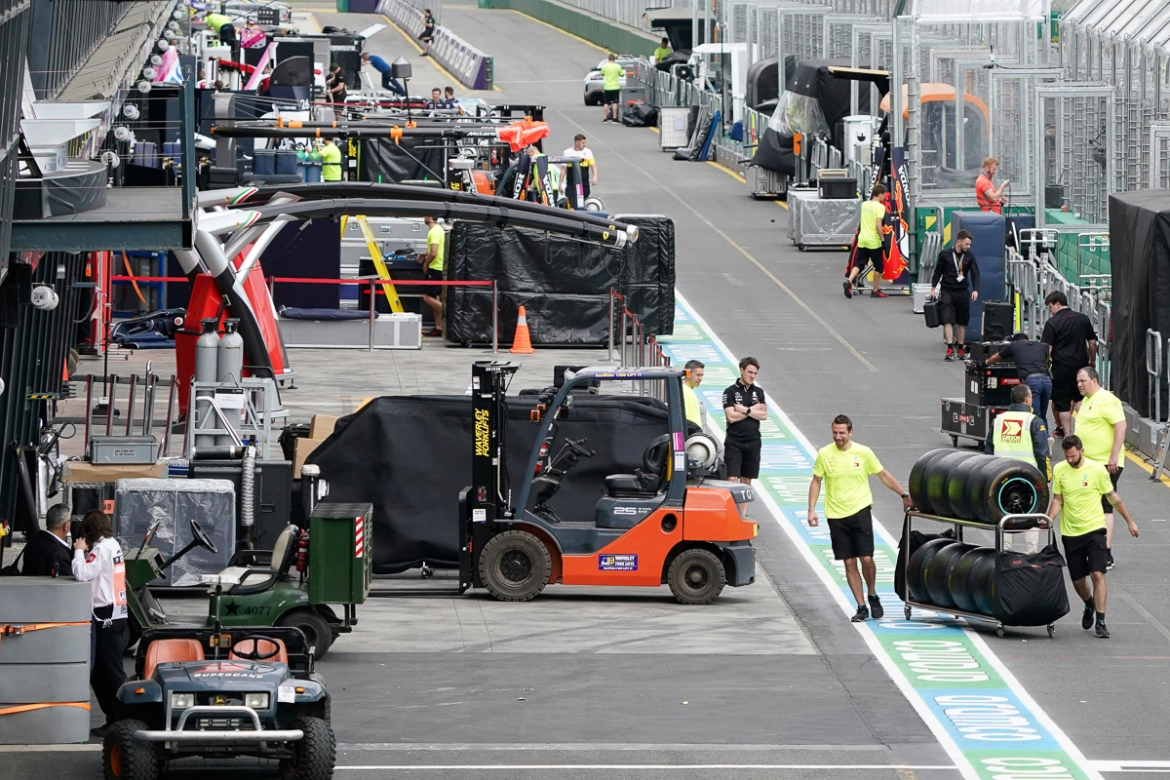Workers pack up in pit lane after the cancellation of the Australian Formula One Grand Prix in Melbourne. The first F1 Grand Prix of the season was cancelled two hours before the first official practice was set to start after organisers relented to pressure to call it off amid the spreading coronavirus. [Michael Dodge/AAP Image via AP]