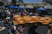 File: A youth walks by carrying loaves of bread as worshippers prepare to pray close to the Damascus Gate of the Old City in Jerusalem on July 25, 2014 [Siegfried Modola/Reuters]