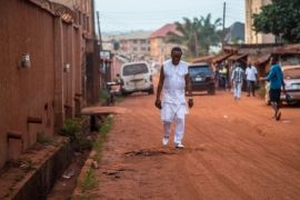 Clinton Kanu walks along the sandy roads of his neighbourhood in Enugu [Chika Oduah/Al Jazeera]