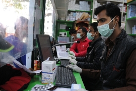 People at a pharmacy in New Delhi wearing protective masks [EPA]
