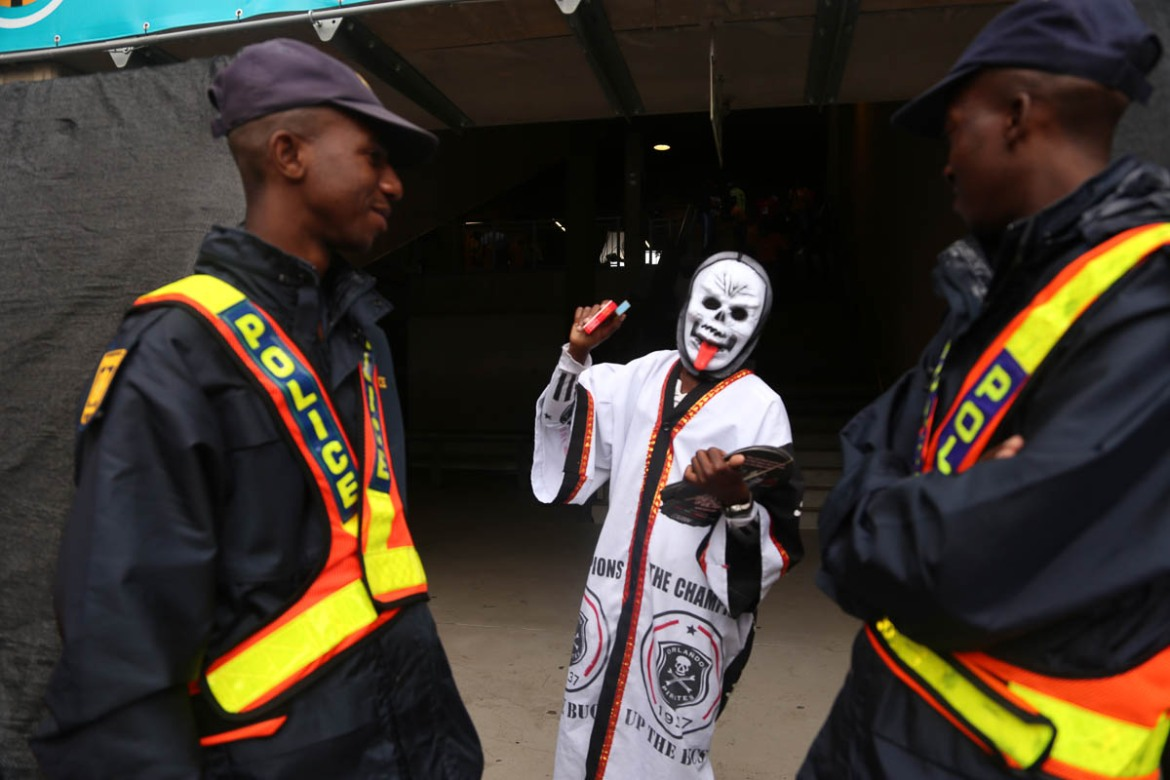 An Orlando Pirates fan gestures to the police as he arrives at the stadium. Masks are worn by many on Derby days to send coded messages to the opposing team. [Antony Kaminju/Al Jazeera]