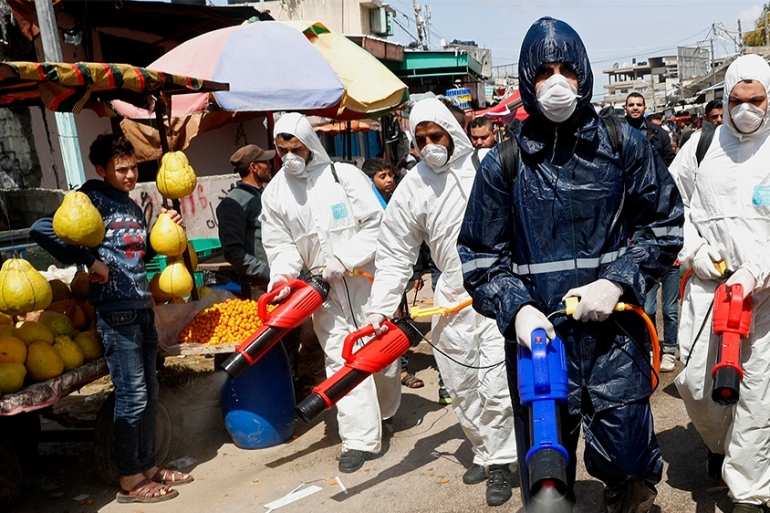 Workers in protective gear spray disinfectant as a precaution against the coronavirus at the main market in Gaza City [File: Adel Hana/AP Photo]