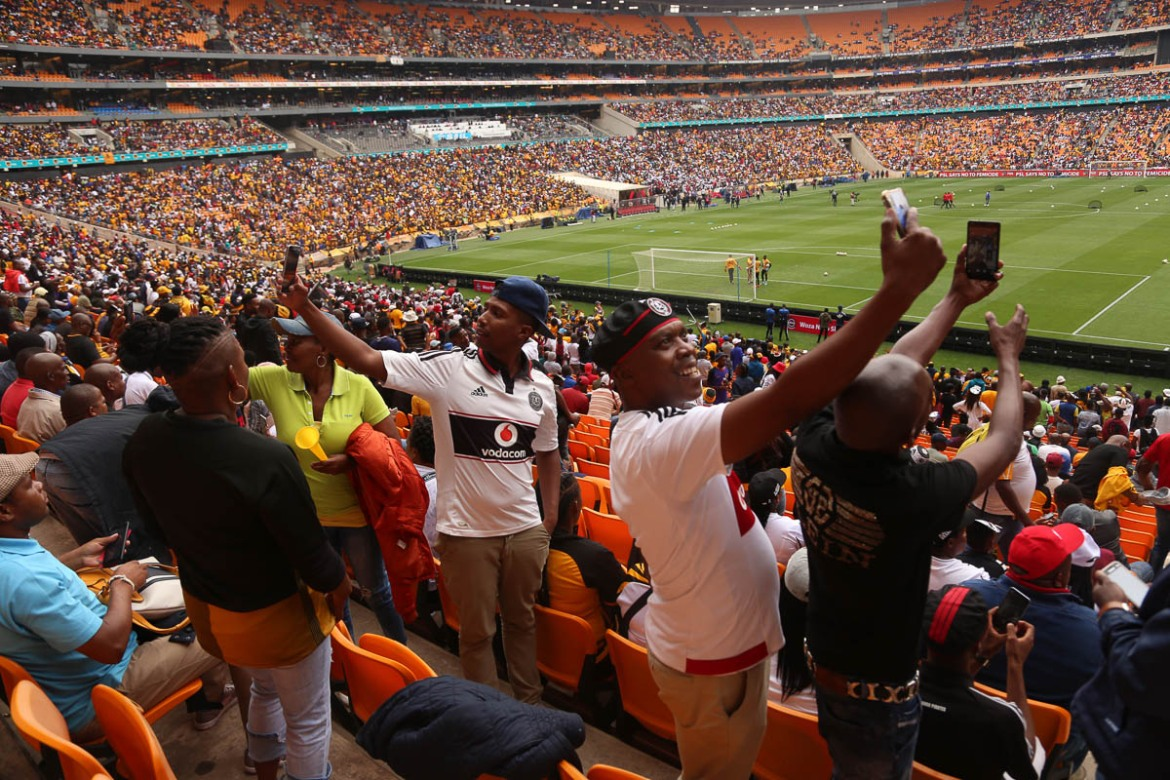 The stands - usually packed to capacity - are awash with gold, black and white - representing the colours of both the Kaizer Chiefs and Orlando Pirates. Fans come from around South Africa, and some even come from neighbouring countries, to attend matches when the two teams meet. [Antony Kaminju/Al Jazeera]