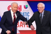 Joe Biden and Bernie Sanders do an elbow bump in place of a handshake before the start of the 11th Democratic candidates' debate in Washington, DC [File: Kevin Lamarque/Reuters]